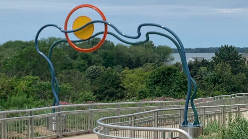 """Workers install a new art piece, """"Sun Gate"""" in the Our West Bayfront."""